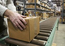 Man putting box on a factory conveyor belt.