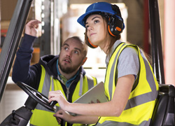 Woman driving a forklift talking to man in warehouse.